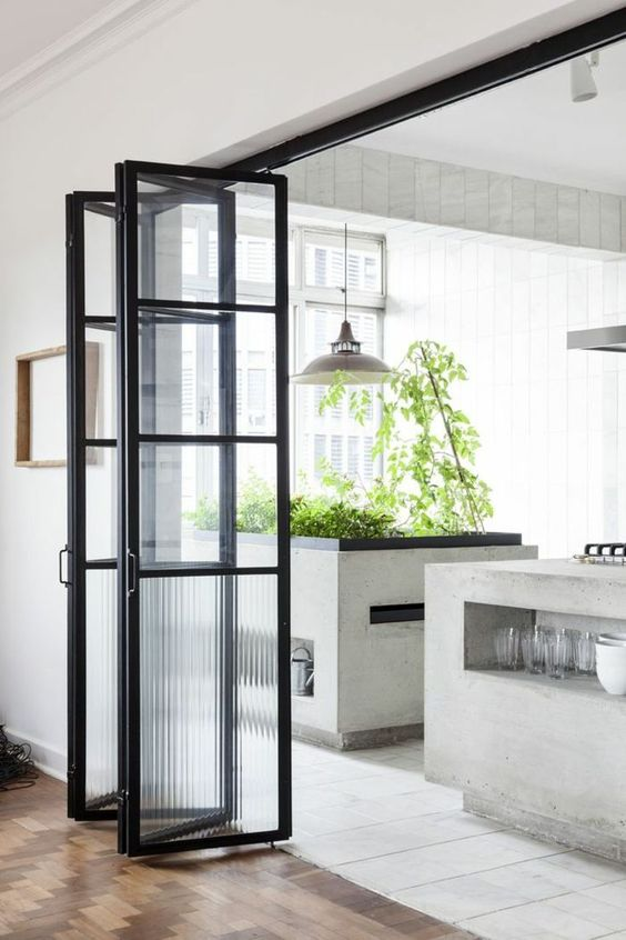 a cool black frame glass folding door with usual and frosted glass is a lovely solution to delicately separate the spaces