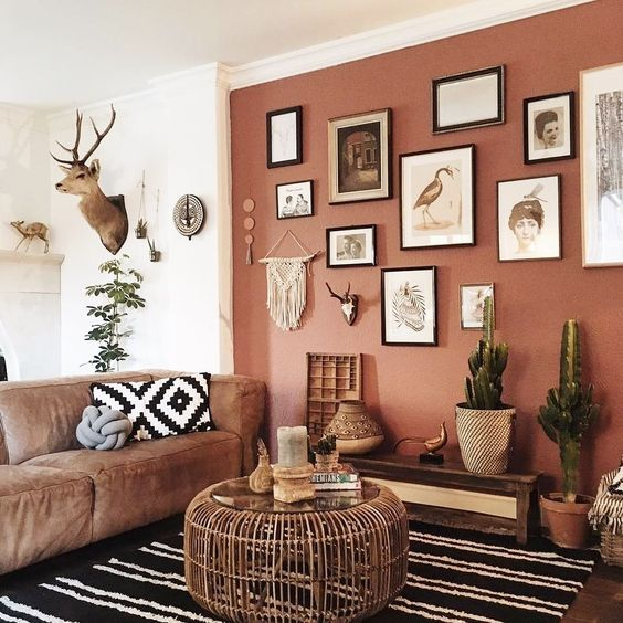 a cool boho living room with a dusty pink accent wall, a brown low sofa, a wooden coffee table, a boho gallery wall and some potted cacti