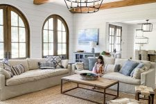 a cool coastal living room with light-stained wooden beams, neutral seating furniture, blue pillows, a coffee table and a large jute rug