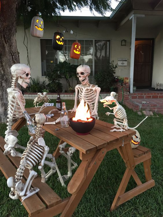a cool outdoor bbq scene done with skeletons and skeleton dogs plus jack-o-lanterns is a very fresh and fun idea