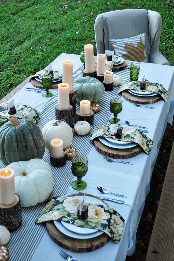 a cool rustic Thanksgiving tablescape with a striped runner, heirloom pumpkins, pillar candles, green glasses, wood slices and floral napkins