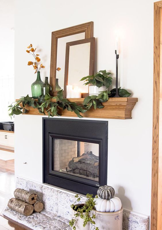 a cool rustic fall mantel with a greenery garland, green bottles with dried blooms, empty frames, mirrors, firewood and stacked heirloom pumpkins