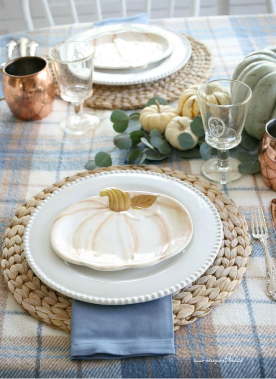 a cool rustic table setting with woven placemats, pumpkin plates and pumpkins, greenery and copper mugs