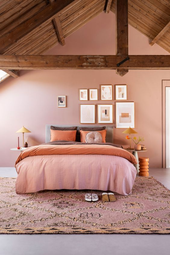 a cozy attic bedroom with a pink accent wall, a grey bed with orange and brown bedding, a gallery wall, nightstands, table lamps and a pink printed rug