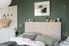 a cozy bedroom with a dark green accent wall, a greige upholstered bed, white nightstands, an artwork and some neutral bedding plus a pendant lamp