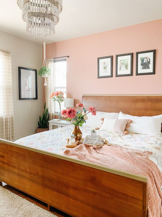 a cozy bedroom with a peachy pink wall, a stained bed, neutral and pink bedding, a grid gallery wall, a beaded chandelier and some potted plants
