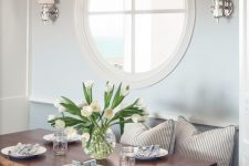 a cozy coastal dining nook with a porthole window and wall lamps looks very refined and very chic