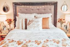 a cozy fall bedroom with an upholstered bed, neutral and orange bedding, a pumpkin blanket, matching nightstands and fall blooms plus elegant table lamps