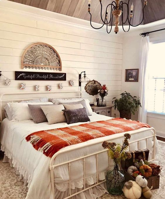 a cozy farmhouse flal bedroom with planked walls, a white forged bed, neutral and plaid bedding, fabric pumpkins in a chest, greenery and dried blooms is welcoming