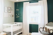 a cozy farmhouse nursery with a dark green accent wall, a white crub and curtains, a dark stained chair, layered rugs and a gilded chandelier