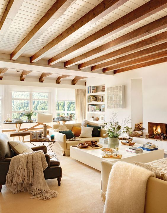 a cozy neutral living room with a fireplace, neutral seating furniture, a large square coffee table and wooden beams, colorful pillows
