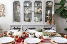 a cozy rustic Thanksgiving table setting with a plaid tablecloth, pumpkins, pinecones, copper mugs, greenery and wood slice placemats