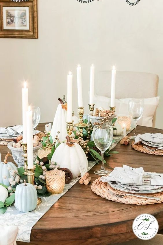 a cozy rustic Thanksgiving tablescape with a printed runner, white and light blue pumpkins, tall candles, berries, woven placemats and candles