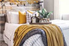 a cozy rustic bedroom with a faux brick accent wall, a reclaimed wooden bed, neutral and mustard bedding, a bright leaf and pumpkin garland and some fabric pumpkins