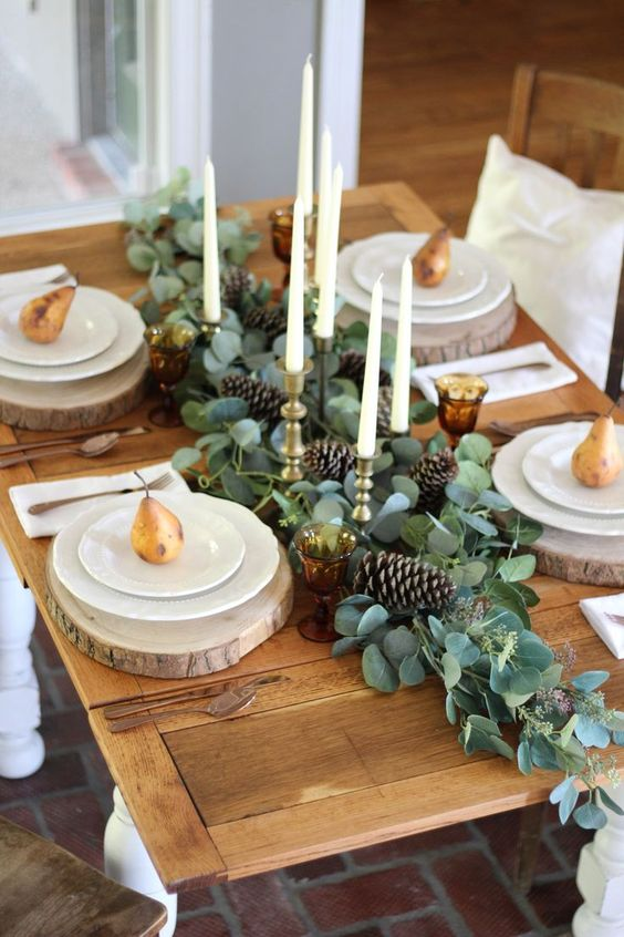 a cozy rustic woodland Thanksgiving tablescape with a greenery and pinecone runner, candles, wood slices and gilded pears
