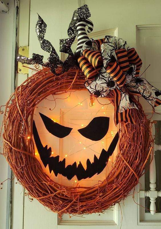a crazy Halloween monster wreath of orange vine, bold bows and a witch's hat, spiders, bows and a scary face with lights