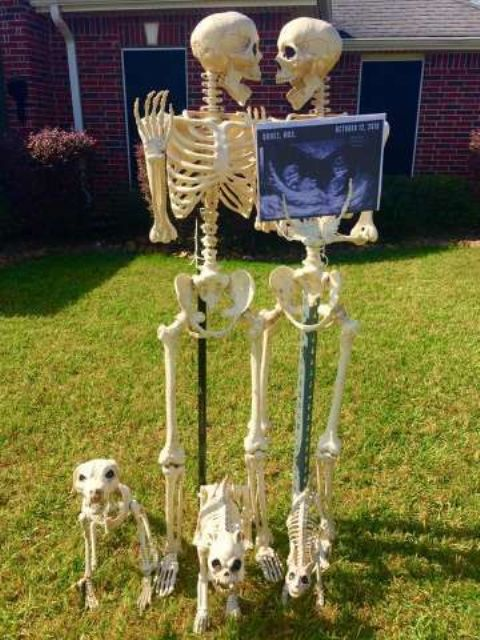 a creative Halloween display with two skeletons and three skeleton dogs possibly portraying the owners of the house
