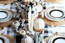 a cute farmhouse Thanksgiving tablescape with a buffalo tablecloth and a pumpkin, white and black pumpkins, cotton, antlers and woven placemats