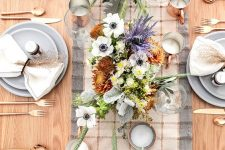 a delicate and cool Thanksgiving tablescape with a plaid runner, grey plates, white and purple blooms, candles