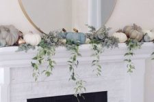 a delicate and subtle mantel decor with pastel and white pumpkins, gilded faux ones and cascading greenery plus an oversized round mirror