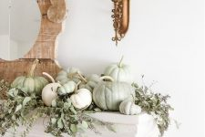 a delicate farmhouse fall mantel with lots of greenery and white and light green natural pumpkins plus a mirror in a wooden frame