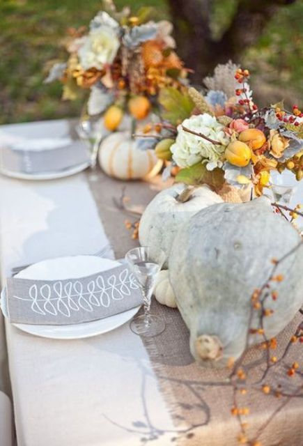 a delicate rustic Thanksgiving tablescape with a grey runner and napkins, heirloom pumpkins and fruits, white plates