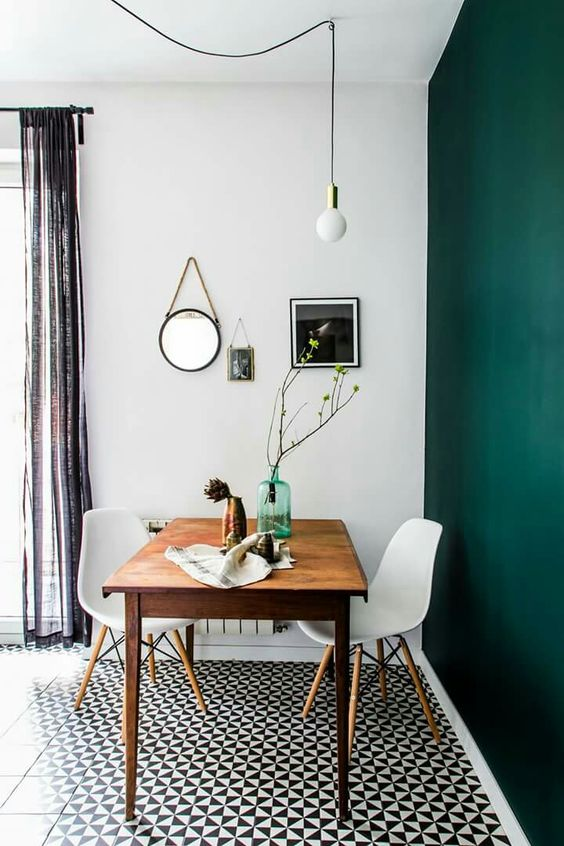 a dining space with a dark green accent wall, a stained table, white chairs, a black and white tiled floor and a pendant bulb plus a mini gallery wall