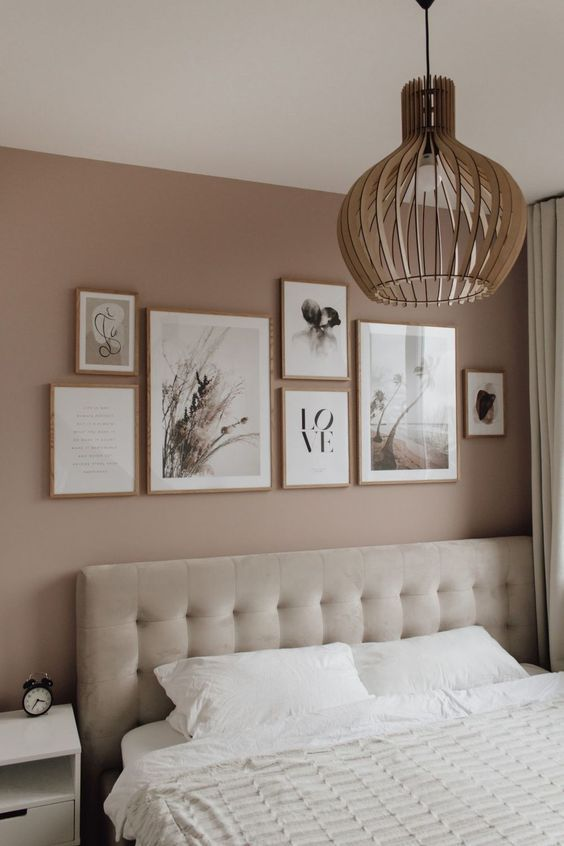 a dreamy Scandinavian bedroom with a dusty pink accent wall, a neutral upholstered bed, a mini gallery wall, a plywood pendant lamp and neutral textiles