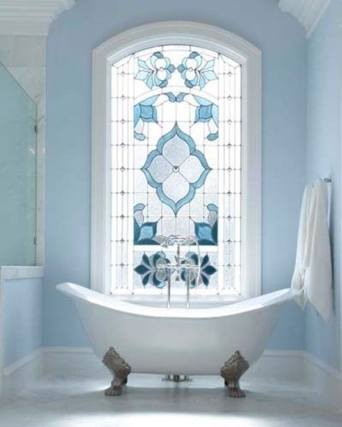 a dreamy light blue bathroom with an oversized window with stained glass, a vintage clawfoot tub, a shower space is amazing