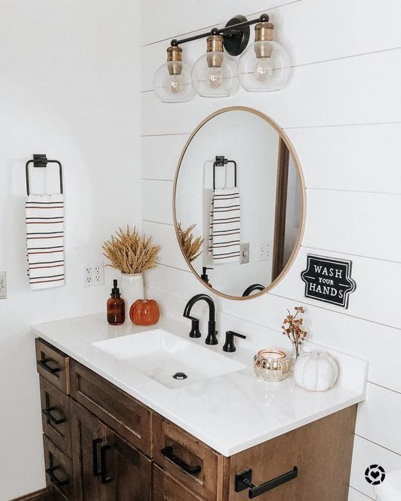 a fall farmhouse bathroom decorated with faux pumpkins, candles, dried blooms and wheat in a vase is a very cozy and lovely idea