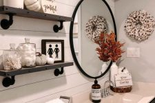 a fall farmhouse bathroom styled with fabric and faux pumpkins, a cotton wreath, dried blooms in a vase and some dried flowers on the shelf