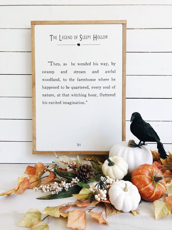 a fall leaf, pinecone and pumpkin arrangement can be topped with a single black bird to feel like Halloween