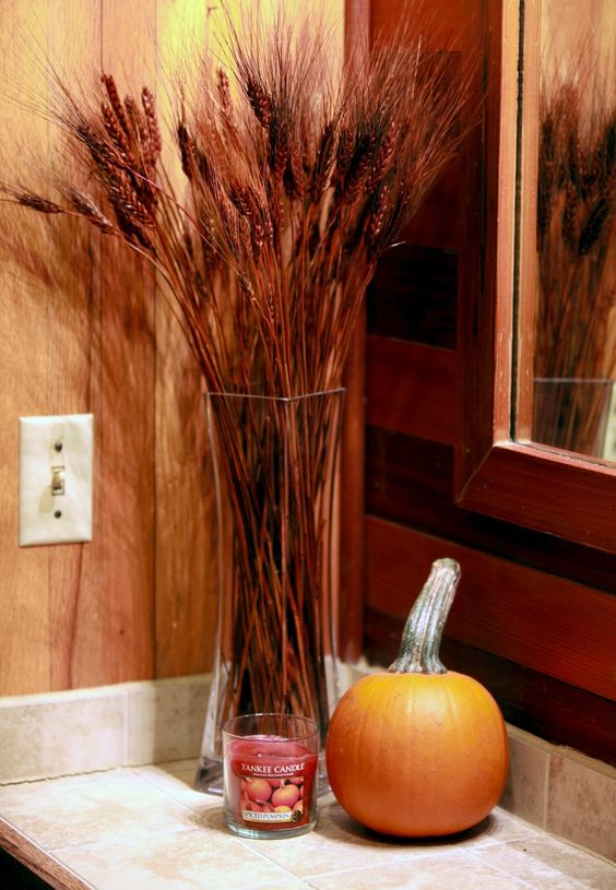 a fall-scented candle, a pumpkin and a wheat arrangement make the bathroom feel rustic and fall-like