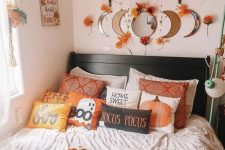 a fall to Halloween bedroom with a black bed, a shelf with potted plants and leaves and pumpkins, pumpkin and ghost pillows and a blanket is cool