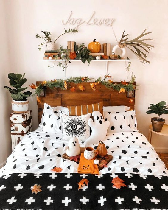 a fall to Halloween bedroom with a stained bed with an evegreen and leaf garland, leaves and a pumpkin on the shelf and fall leaves and gourds on the bed