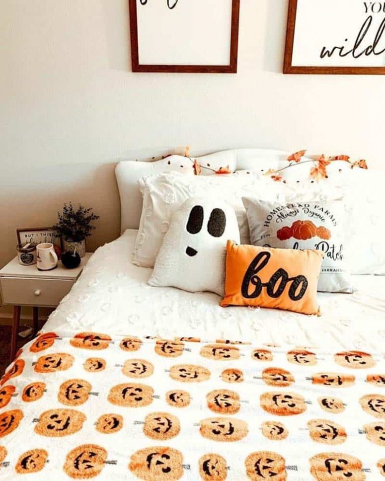 a fall to Halloween bedroom with a white upholstered bed, neutral nightstands, neutral and bold printed bedding, a mini gallery wall and greenery