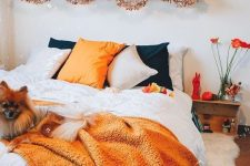 a fall to Halloween bedroom with orange and black bedding, orange blooms, faux pumpkins, bats, letters and some Halloween decor