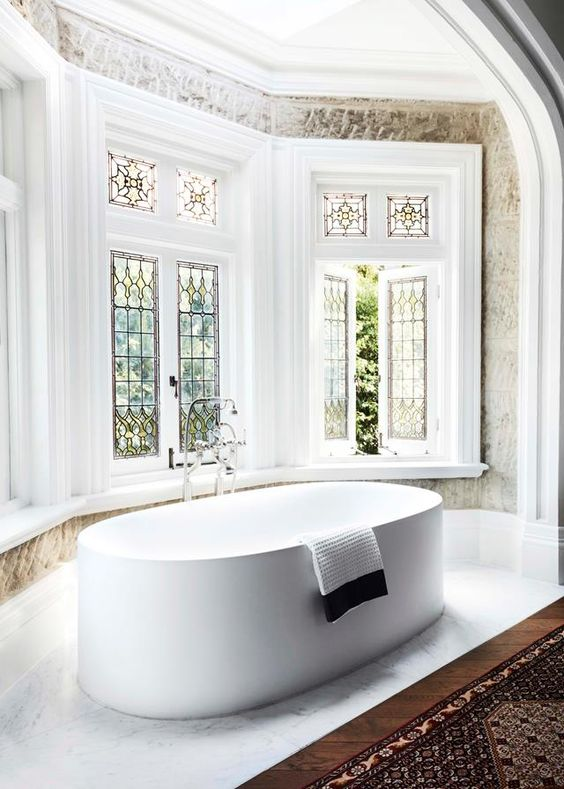 a farmhouse bathroom with a bow window with stained glass, a large oval tub and a printed rug plus lotsof greenery seen through the windows