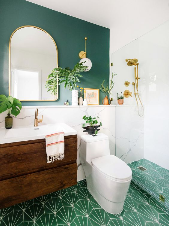 a farmhouse bathroom with a green accent wall, a green tiled floor, a dark stained floating vanity and potted plants plus gilded touches