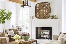 a farmhouse living room with a large brick clad fireplace, neutral seating furniture, a wooden coffee table, wooden beams and layered rugs