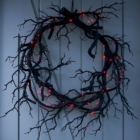 a faux black branch Halloween wreath with lights is a very bold, stylish and spooky decor piece for Halloween