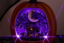 a faux pumpkin with a purple Halloween scene inside – a house with scary trees and a crescent moon with a witch