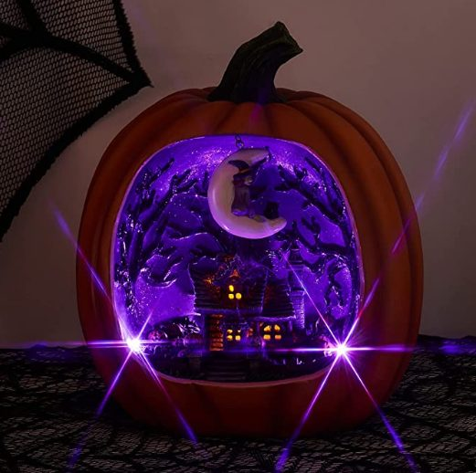 a faux pumpkin with a purple Halloween scene inside - a house with scary trees and a crescent moon with a witch