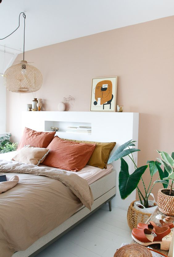 a fresh Scandinavian bedroom with a blush accent wall, a neutral bed with colorful bedding, a white headboard with a niche, a woven pendant lamp