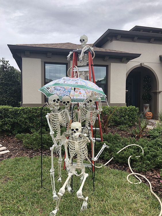 a fun skeleton scene sitting on a ladder and with an umbrella is a cool idea for Halloween outdoor styling