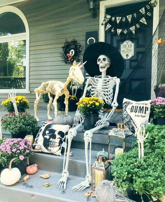 a funny Halloween porch scene with a skeleton and a skeleton unicorn, pumpkins, candle lanterns, buntings and black spider web