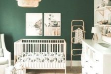 a gender neutral nursery with a dark green accent wall, neutral furniture, open shelves, a woven pendant lamp, a bold green printed rug