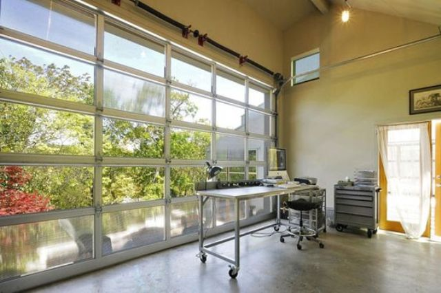 a giant glass garage door opens the home office to the lake outside, isn't it a dream to work next to such a water feature