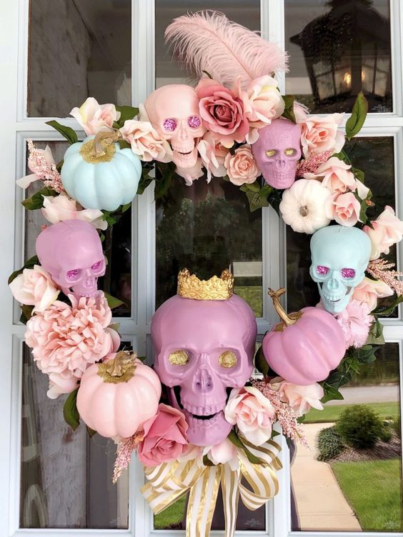 a glam candy-colored Halloween wreath of skulls, faux blooms and feathers is a very cute and lovely idea to go for