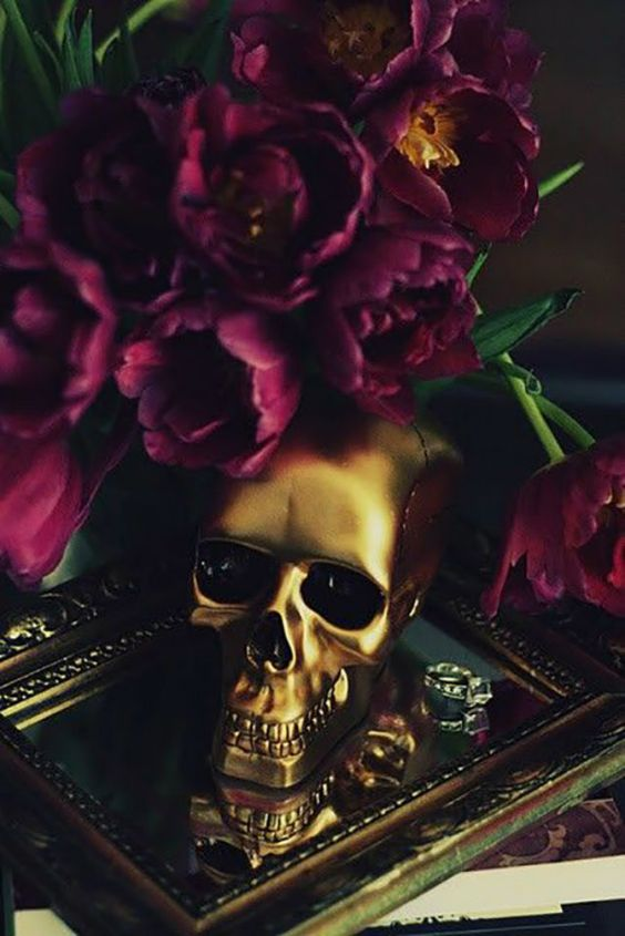 a glam gold skull paired with purple blooms is a stylish idea for decorating your space for Halloween and it looks bright and shiny